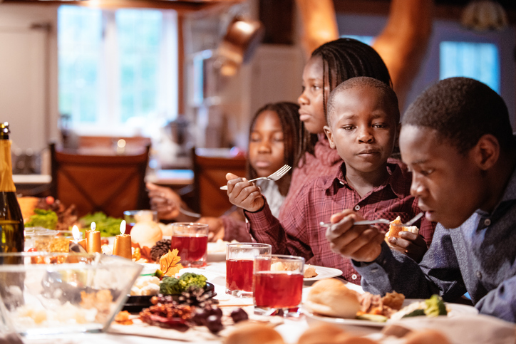 American-African family at table during thanksgiving dinner