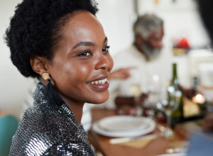Close-up of smiling woman sitting at dining table
