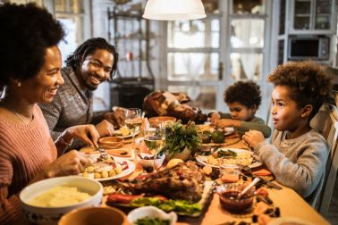 Happy black parents and their kids talking during Thanksgiving dinner at home.