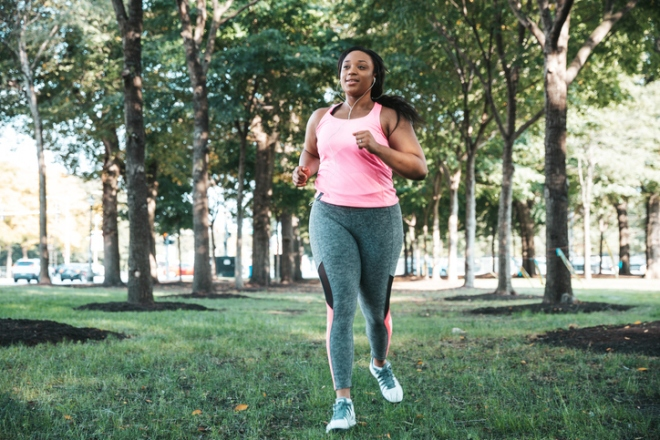 Healthy woman jogging listening to music at the public park