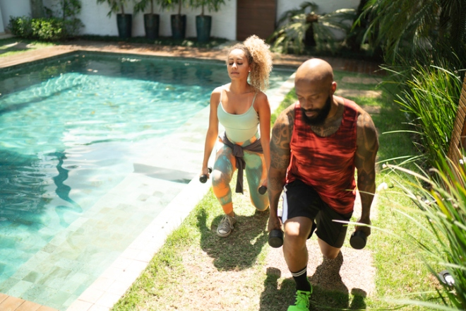 Personal trainer and woman exercising in the yard