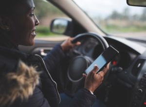 Woman driver scrolling, using smartphone while driving a car.