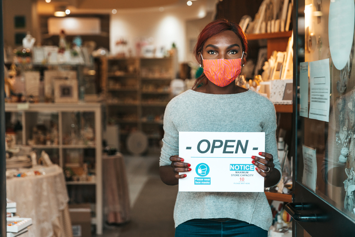 Small business owner holding an -OPEN- sign with the safety measures to respect