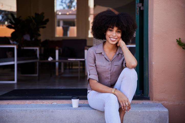 Smiling female entrepreneur sitting at the door of her cafe