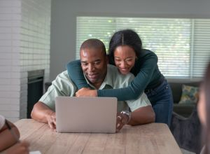 Black father and teenage daughter use video chat to visit with family and friends