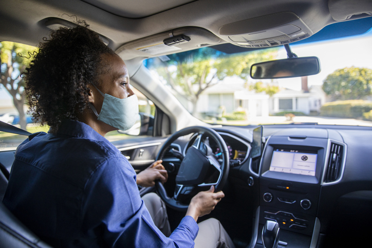 Young Black Woman Driving Car for Rideshare Wearing a Mask