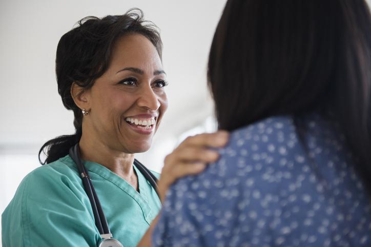 Smiling nurse comforting patient