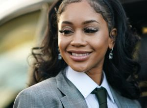 Saweetie in a suit smiling
