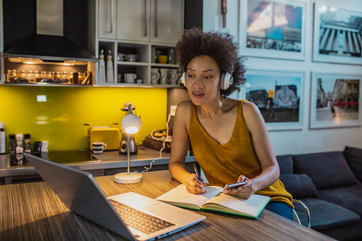 African American woman with headphones is working from home on laptop