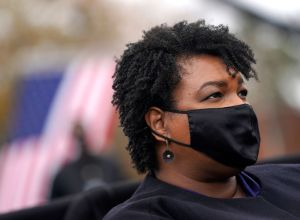 Stacey Abrams wearing mask at political rally was disparaged by a football coach who ended up losing his job over his comments