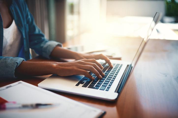 Black woman typing on her laptop