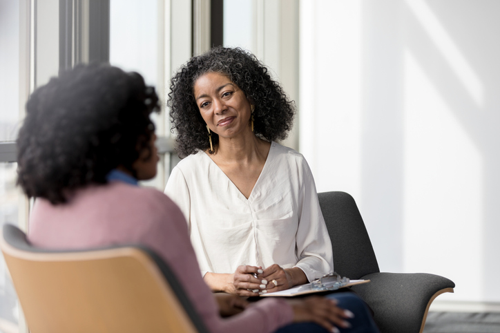 Mature counselor listens compassionately to unrecognizable female client