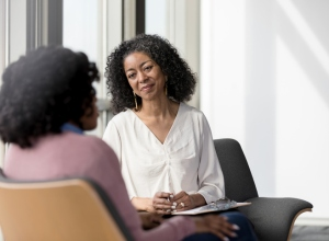 Black female mentor listens compassionately to unrecognizable female client