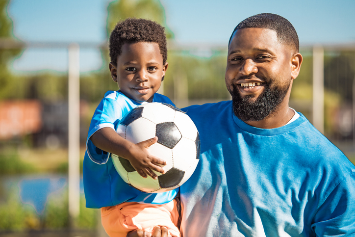 Black father and young son training on the football pitch
