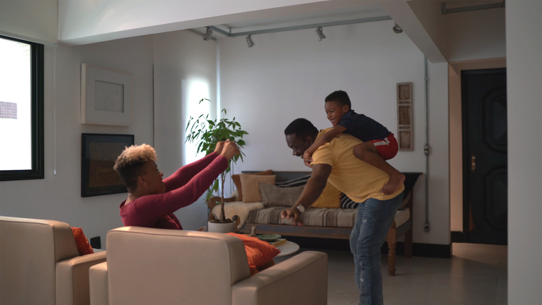 Family playing flying with boy at home