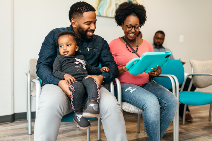 Black family filling out paperwork in doctors office lobby