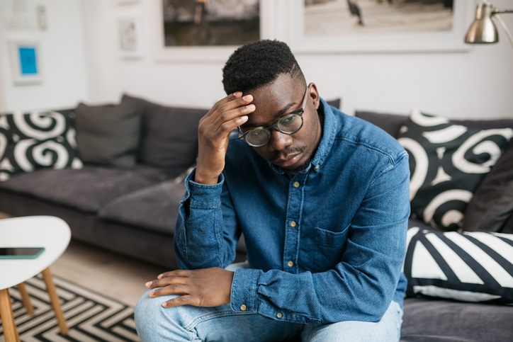 Young depressed African American man sitting at home
