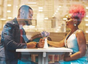 Young beautiful afro couple having romantic dinner
