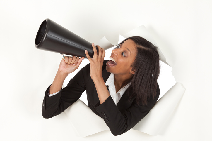 Businesswoman emerging through hole in paper shouting into a bullhorn