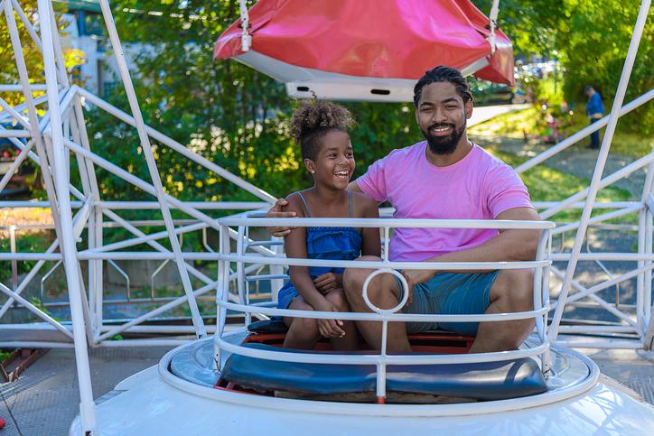 An African-American Family is Enjoying on Ferris Wheel in Amusement Park.