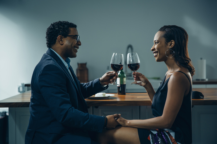 Couple toasting with wine at counter