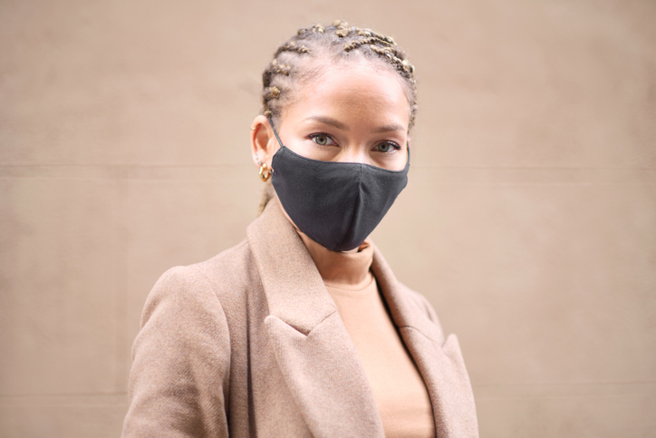 Headshot portrait of a young woman wearing a black protective face mask.