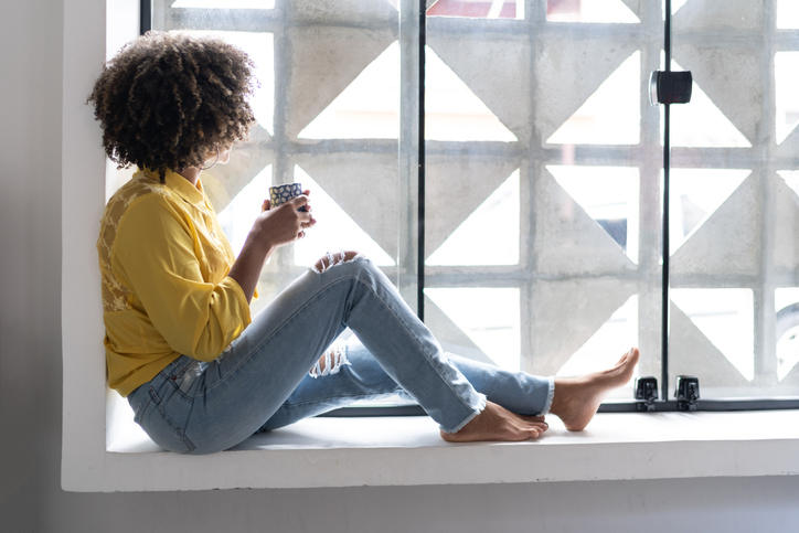 Young woman drinking coffee relaxing on window sill at home