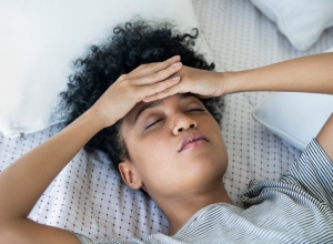 Close-up of young woman suffering from headache