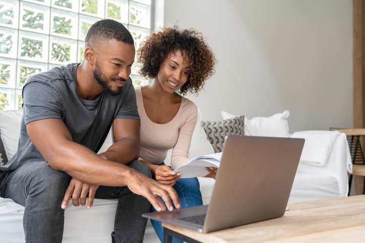 African American couple paying bills online at home