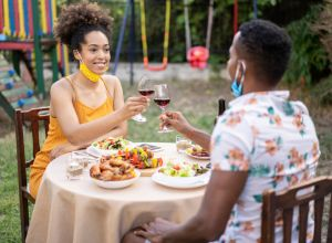 Young couple celebrating in back yard holding glasses of wine in times of social isolation