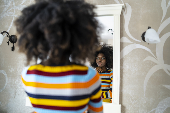 Woman looking at her reflection in the mirror