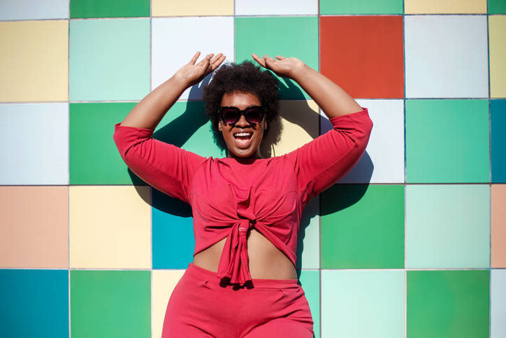 Stylish woman looking excited against multicolored tiled wall