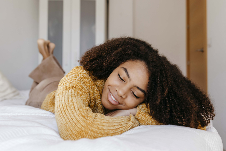 Young woman smiling while lying on bed at home