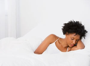 Young African woman sleeping in bed