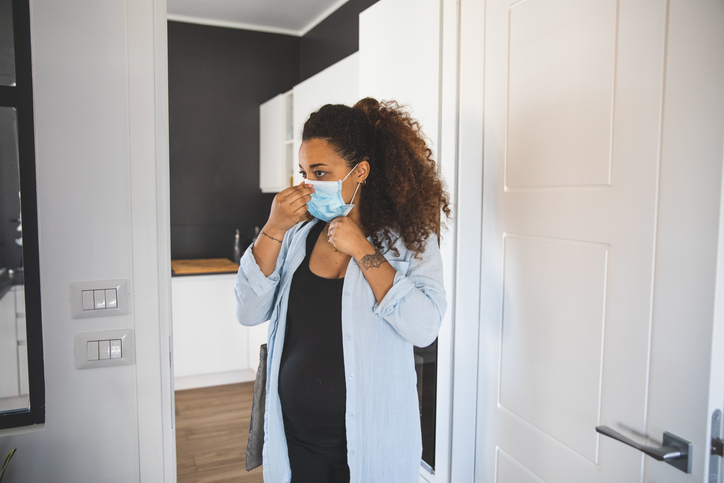 Woman preparing to go out wearing a surgical mask