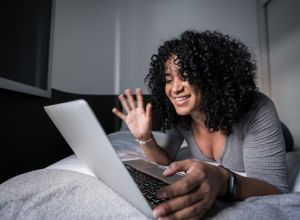 Young woman waving while doing a video call on laptop lying in bed at home