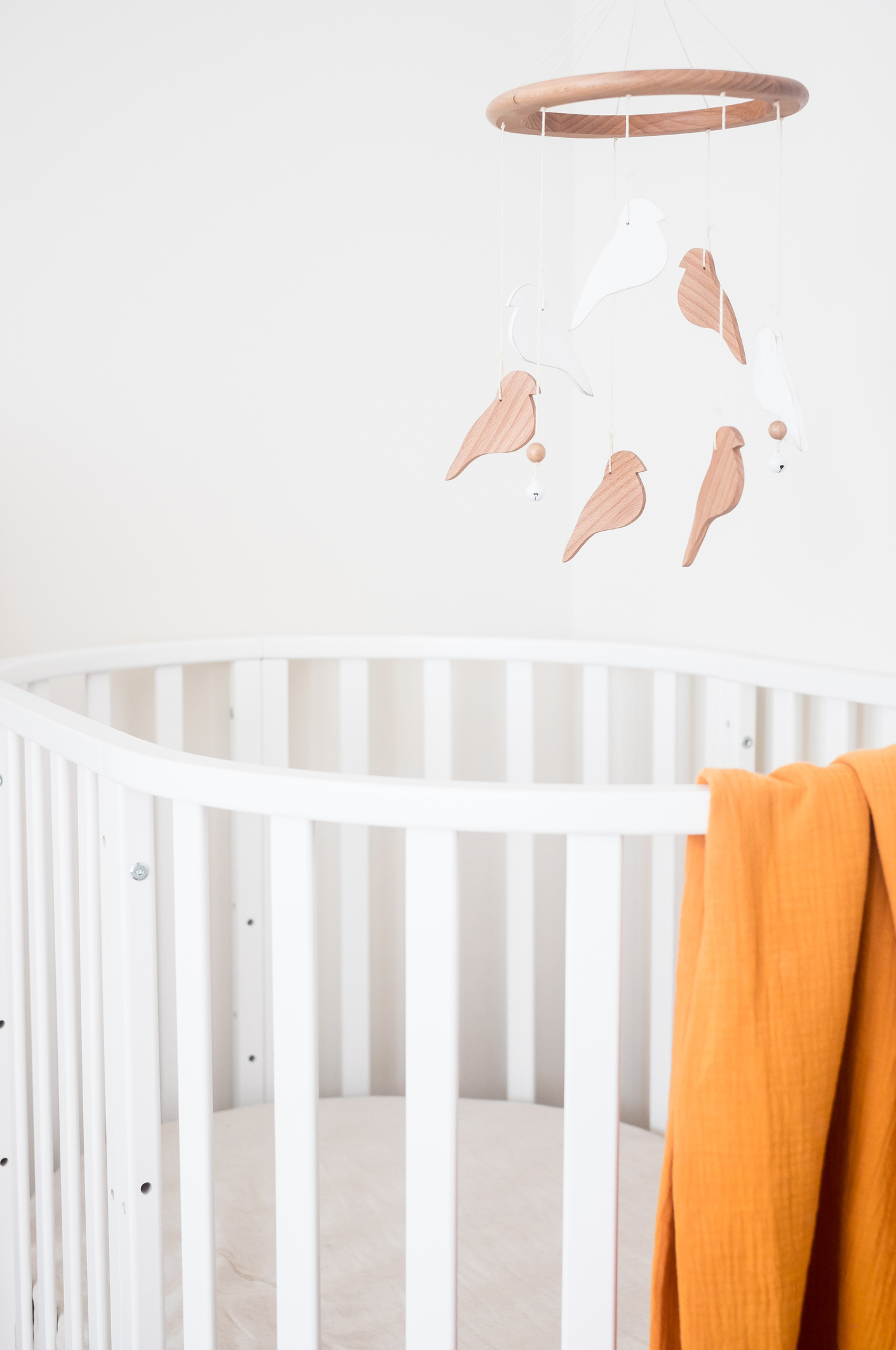 Close up view of baby room with a white baby bed and a baby mobile hanging over the bed, selective focus. Nursery interior.