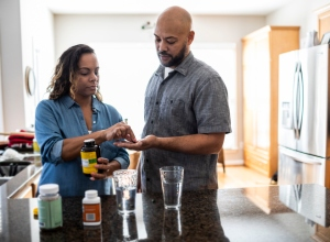 Husband and wife taking vitamins at home