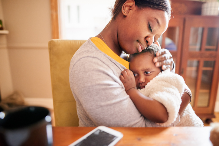 Caring young mother holding her little girl in her arms