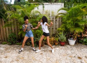 Two Teenage African American Sisters Dancing in the Backyard at Home in Miami