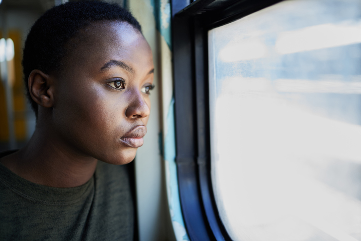 Cropped shot of a young woman looking depressed while staring out the window of a train