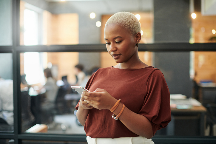 Shot of a young businesswoman using a smartphone in a modern office