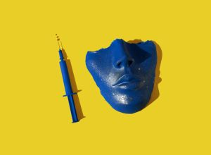 Blue colored syringe and face/ mask on the yellow background.